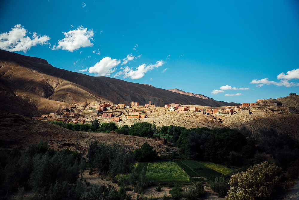 A small mountain village beyond the Dades Gorge en route to Msemrir, Dades Valley, Tinghir Province of Southern Morocco 2016-05-13.<br /> <br /> The road leads out to Msemrir after the gorge, past small villages built up alongside the Oued Dades (Dades River). <br /> <br /> The river runs through the Dades valley and brings life to the region, forming lush green oasis inside the valleys and gorges. <br /> <br /> Water is so treasured here that famers are allocated an annual share by leaders of local tribes and ancient irrigation systems mean they survive by cultivating produce as seasonally and efficiently as possible using what rain each year brings. <br /> <br /> Figs, walnuts, almonds, apples and various vegetables are all farmed in the region, but the most special harvest for the Dades region is the rose season.