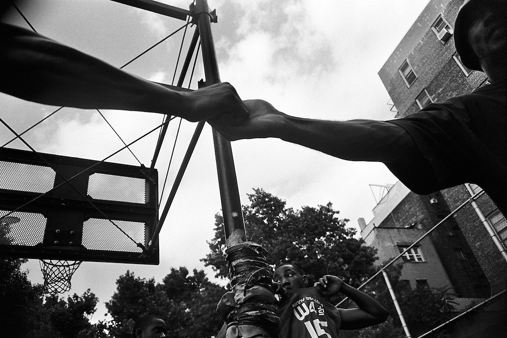 "June 15th 2004. New York, New York. United States..Located in the heart of Greenwich Village, the West 4th Street basketball Court, known as ""The Cage"", offers no seating but attracts the best players and a lot of spectators as soon as spring is around the corner..Half the size of a regular basketball court, it creates a fast, high level of play. The more people watch, the more intense the games get. « The Cage » is a free show. Amazing actions, insults and fights sometimes, create tensions among and inside the teams. The strongest impose their rules. Charisma is present..""The Cage"" is a microcosm. It's a meeting point for the African American street culture of New York. Often originally from Jamaica or other islands of the Caribbean, they hang out, talk, joke, laugh, comment the game, smoke… Whether they play or not, they're here, inside ""The Cage"". Everybody knows everybody, they all greet each other, they shake hands and hug: ""Yo, whasup man?"""