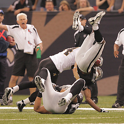 2008 October, 12: Oakland Raiders wide receiver Johnnie Lee Higgins (15) is up ended on a hit by New Orleans Saints linebacker Troy Evans (54) during a week six regular season game between the Oakland Raiders and the New Orleans Saints at the Louisiana Superdome in New Orleans, LA.