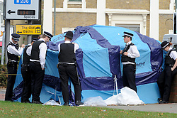© Licensed to London News Pictures. 10/10/2011. London, UK.   Police officers stand over the forensics tent covering the body of a woman killed in a stabbing in Bexleyheath, South London today (10/10/2011). Photo credit : Grant Falvey/LNP