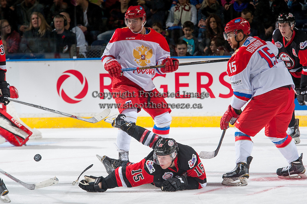 KELOWNA, CANADA - NOVEMBER 9: Ivan Igumnov #15 of Team Russia checks Jansen Harkins #15 of Team WHL to the ice on November 9, 2015 during game 1 of the Canada Russia Super Series at Prospera Place in Kelowna, British Columbia, Canada.  (Photo by Marissa Baecker/Western Hockey League)  *** Local Caption *** Ivan Igumnov; Jansen Harkins;