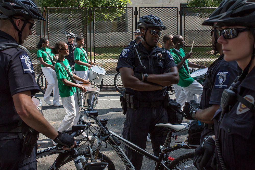 Police officers keep watch as a marching band, part of a Labor Day parade and march, passes near the security fence for the Democratic National Convention on Monday, September 3, 2012 in Charlotte, NC.