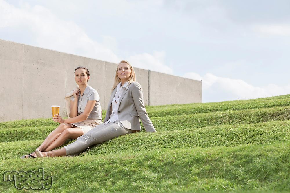 Full length of relaxed businesswomen in formals sitting on grass steps against sky
