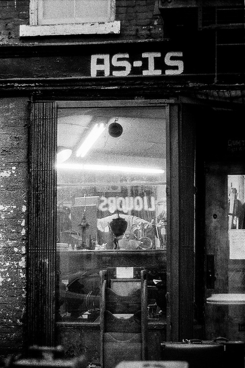 This image captures what the photographer knew would soon be lost. Rents and upscale stores do not allow this kind of offbeat store to exist any longer. The dark lamp near the bottom of the window is perfectly balanced against a hat  hanging from a chain--a deliberate composition. The gritty brick facade is a perfect frame. The neon sign from a liquor store across the street is reflected in the window. Wonderful to come across a place like this. The irony of the title has been pointed out by museum curators. Night. Black and white.