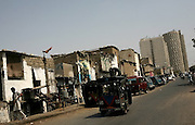 A motor rickshaw passes in front of a road near the business and financial hub of Karachi, Pakistan.