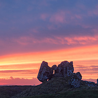 A beautiful sunset backlights the remains of Clonmacnoise Castle, County Offaly, Ireland