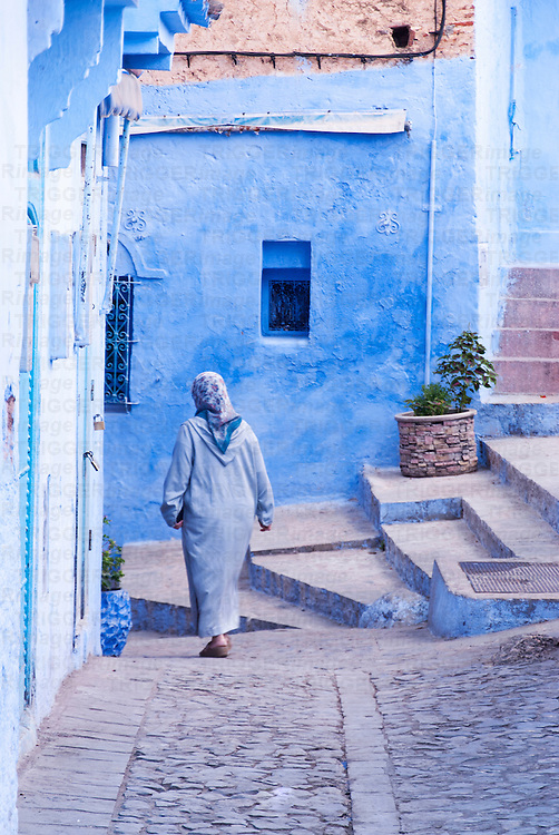 A woman draped in blue, walks in a blue city, Chefchauoen, Morocco