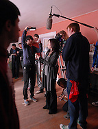 "December 6, 2009- Assistant Lighting Director, junior Masakazu Iwabu (center left), discusses options for lighting a scene with Lighting Director, junior Garrett Williams (center right), while the Director of Photography, senior Kristina Carucci sets up the camera's position behind actress Jojo Marino on the set ""The Last Laugh"" in Dorchester, MA."