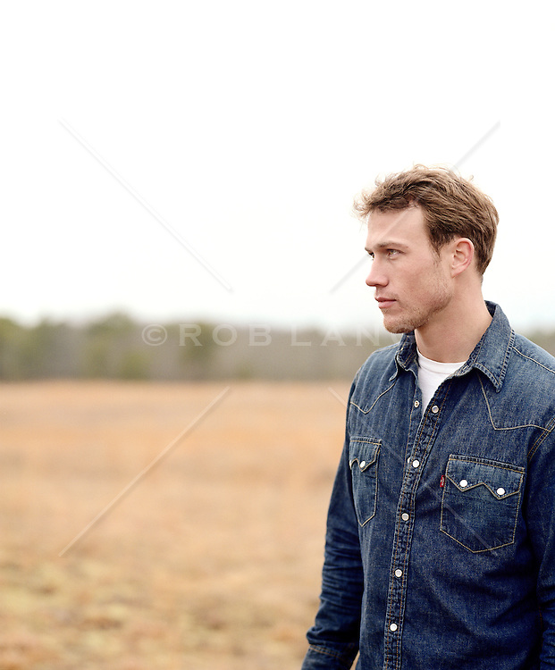 Man outdoors in a tree lined field