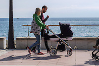 Young couple walking with pram seafront promenade Estepona Malaga Province Spain January 2017, 201701313265<br />