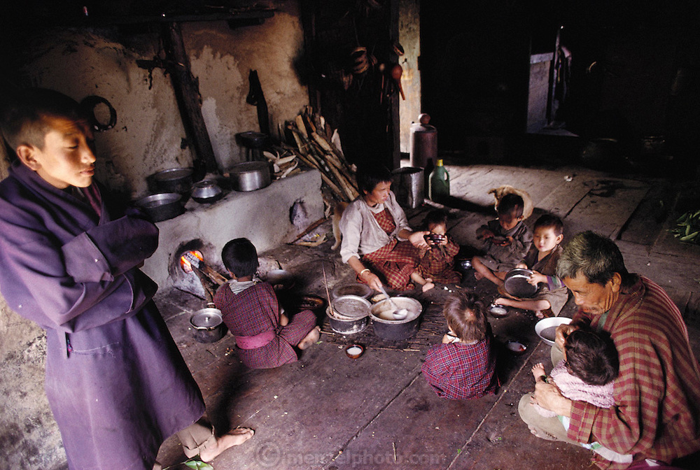 Especially fond of the children, Uncle Kinley Dorji (seated at right) has given up marriage to help with childcare in his sister Nalim's house. A typical task: feeding a weekend breakfast of sweet, thick rice soup to Tandin Geltshin, one of the two-year-olds. His namesake and nephew, Kinley (standing at left) observes the jumble of children from the lofty distance of his 17 years. A student at a boarding school an hour's walk away, he is home only for weekends. Namgay and Nalim's family lives in Shingkhey Village, Bhutan. Published in Material World: A Global Family Portrait, pages76-77.