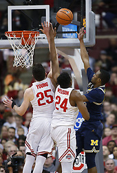 December 4, 2017 - Columbus, OH, USA - Michigan Wolverines guard Muhammad-Ali Abdur-Rahkman (12) scores against Ohio State Buckeyes forward Kyle Young (25) and Ohio State Buckeyes forward Andre Wesson (24) during the first half on Monday, Dec. 4, 2017, at Value Center Arena in Columbus, Ohio. (Credit Image: © Fred Squillante/TNS via ZUMA Wire)