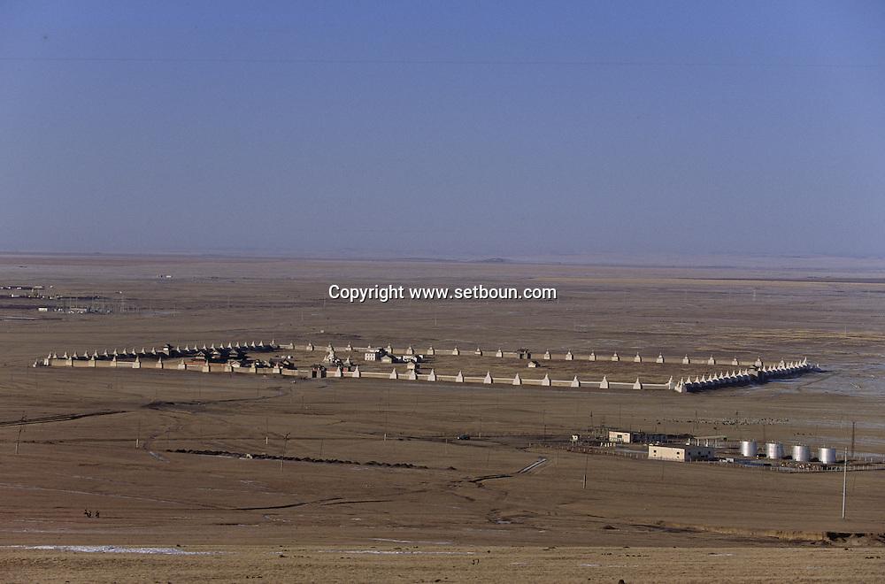 Mongolia. Erden Zuu monastery. Karakorum /   EnHiver monastère de Erden Zuu/  Muraille de stupas entourant le monastère de ERDENI ZUU (XVI me siècle). Érige en 1743, ce mur d'enceinte n'etait à l'origine qu'une sorte de remblai en terre argileuse et graviers, d'une epaisseur de 2,50 mètres environ. Reconstruit en 1804 en briques peintes en blanc avec 56 stupas ou suburgan encastres à espace regulier, ce rempart avait une fonction defensive. Avec le temps, les stupas ont augmente pour atteindre le nombre actuel de 108 : 25 de chaque côte et 2 à chaque angle. (QARAQORIN,