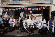 Spectators await the arrival of racers at a nearby French cafe on the first day of competition of the London 2012 Olympic 250km mens' road race. Starting from central London and passing the capital's famous landmarks before heading out into rural England to the gruelling Box Hill in the county of Surrey. Local southwest Londoners lined the route hoping for British favourite Mark Cavendish to win Team GB first medal but were eventually disappointed when Kazakhstan's Alexandre Vinokourov eventually won gold.