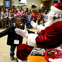 Thomas Wells | BUY at PHOTOS.DJOURNAL.COM<br /> Brasley Watkins rushes to give Santa one last hug before leaving his visit with him at Renasant Bank on Monday in Tupelo. Santa spent Monday and Tuesday at the bnk visiting with several local head starts and primary school children.