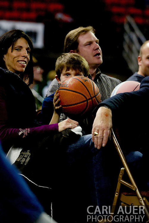 11/25/2006 - Anchorage, Alaska: A young fan pokes his eyes over the game ball the officials asked him to hold onto during a media time out as Hawaii beat Pacific 71-60 to give the Warriors a third place finish in the 2006 Great Alaska Shootout<br />