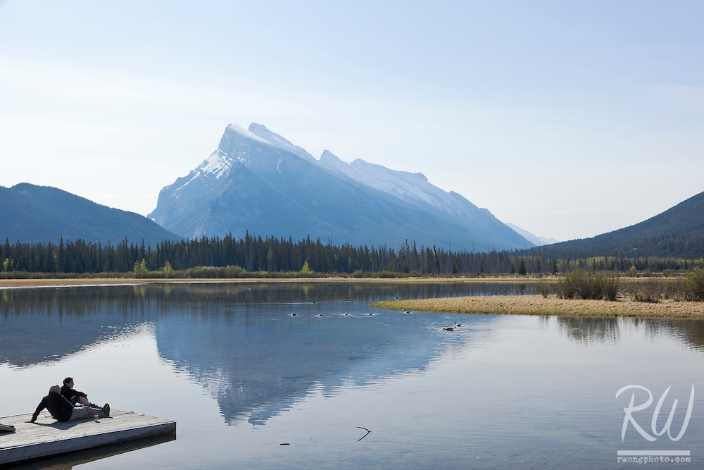Couple Sitting on Shoreline of Vermillion Lakes, Banff National Park, Alberta, Canada
