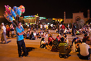 Kashgar: A ballon vendor along with local Uighur families gather on Id Khar Mosque square nightly to watch Uighur TV broadcast TV shows and films on giant screen in the square...Despite the migration of millions of Han Chinese to the western part of the Xinjiang Uighur Autonomous Region, the Uighur community continue to practice their muslim culture and resist the suppression of their cultural and religious traditions by the Chinese government....The chinese government has been criticised for the redevelopment of the old city, which has involved the destruction of many of the old houses in the town that were built without regulation, officials claiming them to be overcrowded and uncompliant with earthquake codes...Many in the chinese government believe Kashgar to a breeding ground for Uighur separatists, who Beijing claim to have links to terrorism...The european parliament has called for a halt to the cultural destruction of Kashgar, suggesting that Kashgar be added tot he UNESCO World heritage 'Silk Road' project, and calling on the chinese government to develop a genuine Han-Uighur dialogue to adopt more inclusive and comprehensive economic policies in Xinjiang in order to protect the cultural identity of the Uighur population..©JTanner/July 2011