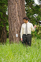 Businessman standing next to a tree holding a extension cord looking down at an electrical outlet on the trunk of a tree in a grassy field.