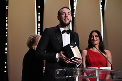 """Director Vasilis Kekatos receives the Short Film award for """"The Distance Between Us and The Sky"""" as Jury Member Nadine Labaki (R) looks on on stage during the Closing Ceremony of the 72nd annual Cannes Film Festival on May 25, 2019 in Cannes, France. Photo by David Niviere/ABACAPRESS.COM"""