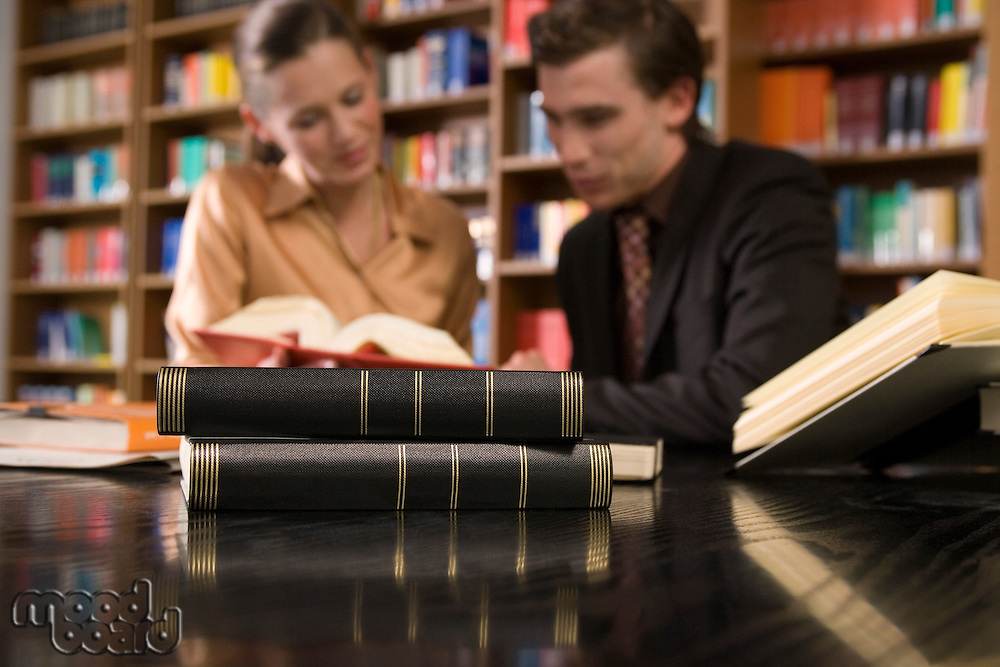 Young man and woman studying at desk in library focus on books in foreground