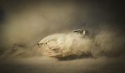A piece of excavation equipment battles a dust cloud as part of an industrial photography session near Del Rio, Texas.