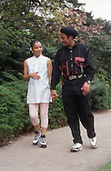 Pregnant woman with partner walking in park,