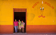 Three women greet the camera at the entrance of a chicken restaurant in the Old Spanish Colonial town of Chinandega, Nicaragua. Nicaragua is one of the poorest nations in the Western Hemisphere. The country has struggled to improve its economy after decades of war and natural disasters. The recent re-election of Daniel Ortega has fueled many different sentiments throughout the world.