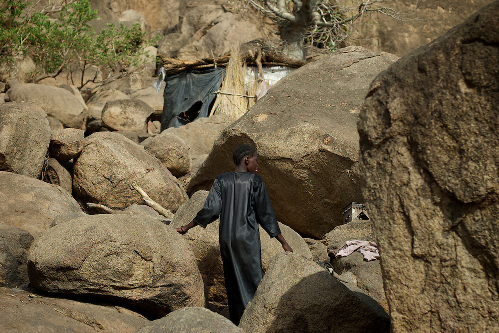 April 28, 2012 - Buram, Nuba Mountains, South Kordofan, Sudan: A Nuba woman walks among the rocks near her improvised home in the caves outside Buram village in South Kordofan's Nuba Mountains...Since the 6th of June 2011, the Sudan's Army Forces (SAF) initiated, under direct orders from President Bashir, an attack campaign against civil areas throughout the South Kordofan's province. Hundreds have been killed and many more injured...Local residents, of Nuba origin, have since lived in fear and the majority moved from their homes to caves in the nearby mountains. Others chose to find refuge in South Sudan, driven by the lack of food cause by the agriculture production halt due to the constant bombardments of rural areas. (Paulo Nunes dos Santos/Polaris)