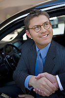 Business man sitting in car, shaking hands