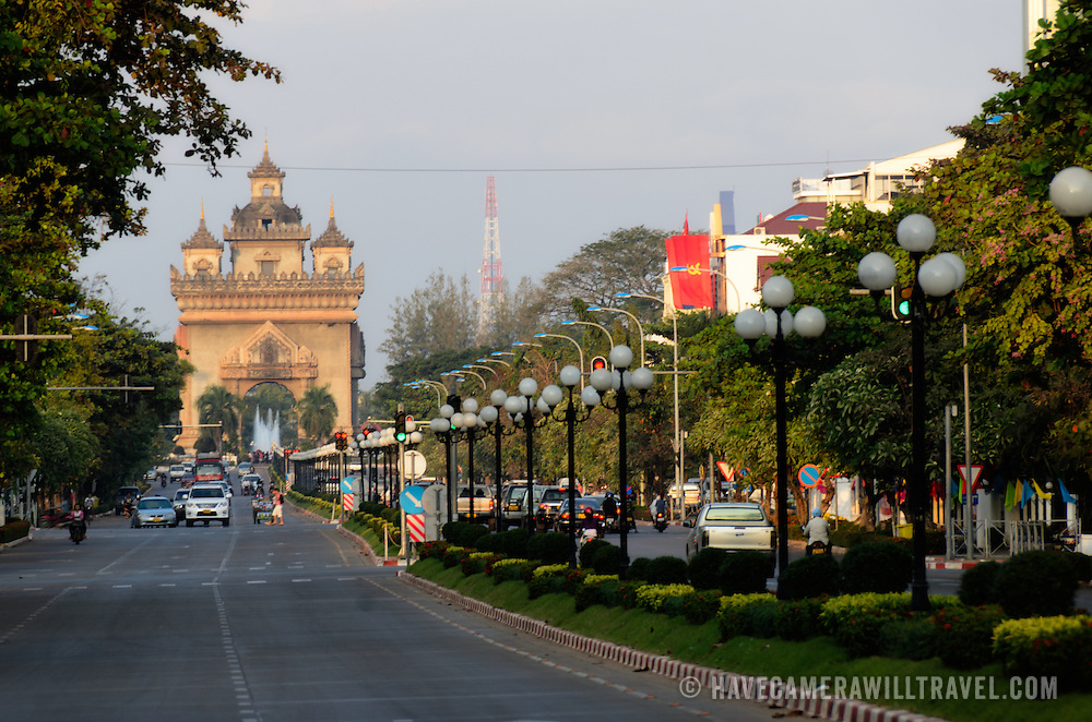"View down Avenue Lane Xang in Vientiane, Laos, in front of the Presidential Palace. At left, in the distance is Patuxai (Victory Gate or Gate of Triumph), a war memorial. It's also known colloquially as the ""vertical runway"" because it's made from concrete supplied by American aid to build an airport that was never finished. It is also sometimes transliterated as Patuxai, Patuxay, Patousai and Patusai"