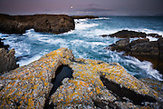 A choppy sea at the craggy coastline at Rhoscolyn with the moon rising over the Welsh mainland.