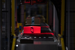 """© Licensed to London News Pictures . 04/12/2019. Manchester , UK . Sealed packages are scanned on a conveyor belt for onward dispatch inside the """"MAN1"""" Amazon fulfilment centre warehouse at Manchester Airport in the North West of England . Photo credit : Joel Goodman/LNP"""
