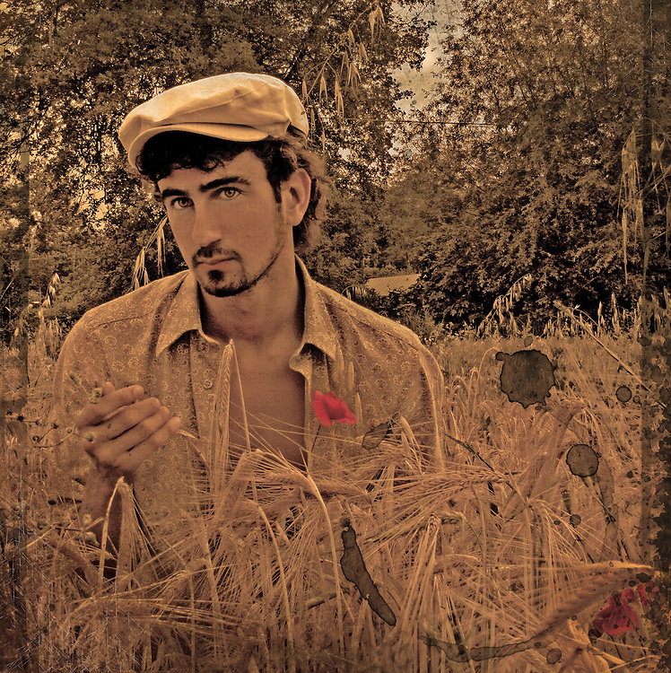 A young man wearing a flat cap standing in a corn field