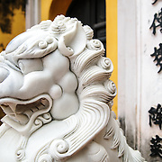 Side view of an ornately carved white marble lions guard the entrance to a gate at the One Pillar Pagoda next to the Ho Chi Minh Museum in the Da Binh district of Hanoi, Vietnam.