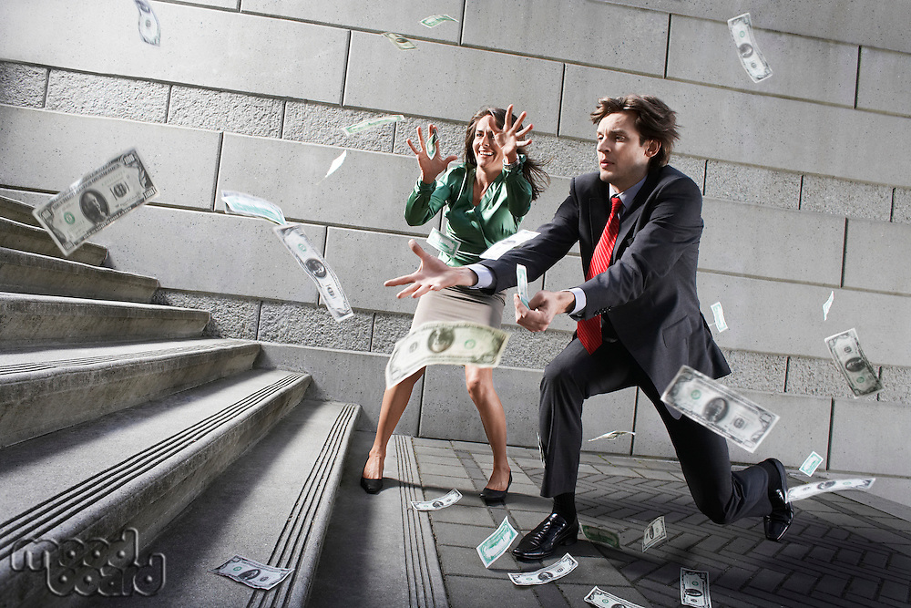 Busines man and woman catching falling money on steps