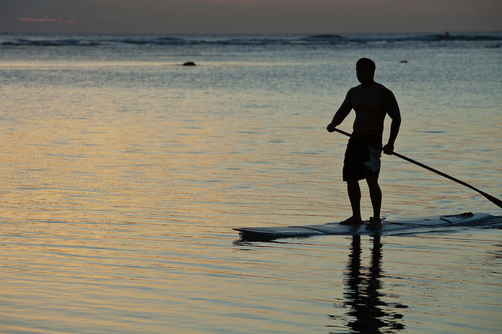 Stand up board paddler in silhouette at Ala Moana Beach Park