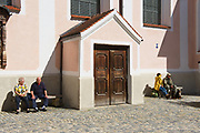Mittenwald, Germany - September 01, 2010: Unidentified, senior tourists relax at the street next to the cathedral of Mittenwald, Germany.