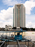 A cross river ferry works the Chao Phraya river. The Peninsula Hotel towers on the far side.