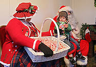 Griffin Shroyer (center), 2, of Cedar Rapids receives a candy cane from Mrs. Claus while sitting on Santa Claus' lap during Christmas in the Park and Peppermint Walk at City Square Park in Marion on Friday evening, December 2, 2011. (Stephen Mally/Freelance)