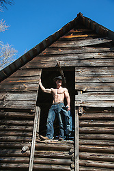 cowboy without a shirt standing in a rustic barn doorway