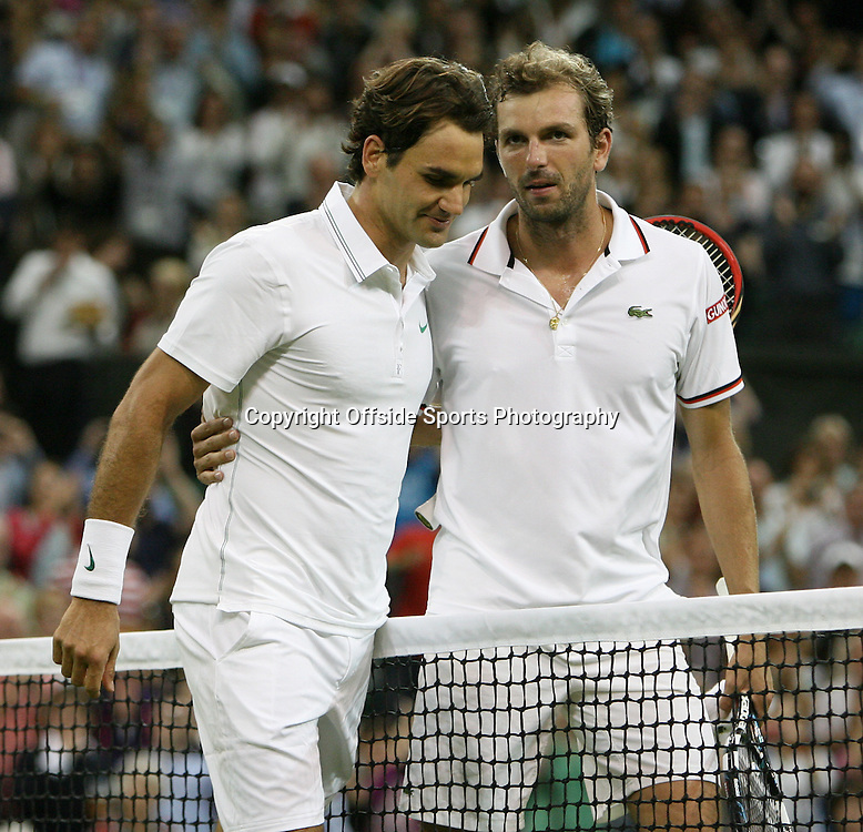 29/06/2012 - Wimbledon (Day 5) - Roger FEDERER (SUI) vs. Julien BENNETEAU (FRA) - The two players embrace at the net after the match, which Roger Federer (L) won - Photo: Simon Stacpoole / Offside.
