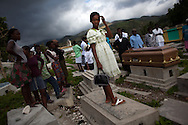 A girl stands on a grave in a cemetery just outside of the town of La Branle, Haiti during a funeral, Saturday, December 4, 2010.  Like many other riverside towns in the Artibonite, region, La Branle has been hit hard by the recent cholera epidemic that has left over 3,000 people dead countrywide. (photo by Allison Shelley)