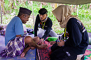 Medical student volunteers Hasmadi and Dewi checks the health condition of Syamsul 75 who isn't able to walk.  A powerful 7.5 earthquake magnitude struck off the coast of Donggala (epicentre) Central Sulawesi, Indonesia on Sept. 28th causing a tsunami and destroying many homes.