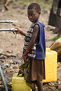 A girl fills jericans of water from a pipe in the Mugunga II IDP camp on the outskirts of Goma, Democratic Republic of Congo, on Wednesday December 17, 2008.