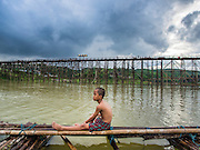 15 SEPTEMBER 2014 - SANGKHLA BURI, KANCHANABURI, THAILAND: A boy sits on a temporary bamboo bridge that is being used while the Mon Bridge, in the background, is repaired. The 2800 foot long (850 meters) Saphan Mon (Mon Bridge) spans the Song Kalia River. It is reportedly second longest wooden bridge in the world. The bridge was severely damaged during heavy rainfall in July 2013 when its 230 foot middle section  (70 meters) collapsed during flooding. Officially known as Uttamanusorn Bridge, the bridge has been used by people in Sangkhla Buri (also known as Sangkhlaburi) for 20 years. The bridge was was conceived by Luang Pho Uttama, the late abbot of of Wat Wang Wiwekaram, and was built by hand by Mon refugees from Myanmar (then Burma). The wooden bridge is one of the leading tourist attractions in Kanchanaburi province. The loss of the bridge has hurt the economy of the Mon community opposite Sangkhla Buri. The repair has taken far longer than expected. Thai Prime Minister General Prayuth Chan-ocha ordered an engineer unit of the Royal Thai Army to help the local Mon population repair the bridge. Local people said they hope the bridge is repaired by the end November, which is when the tourist season starts.    PHOTO BY JACK KURTZ