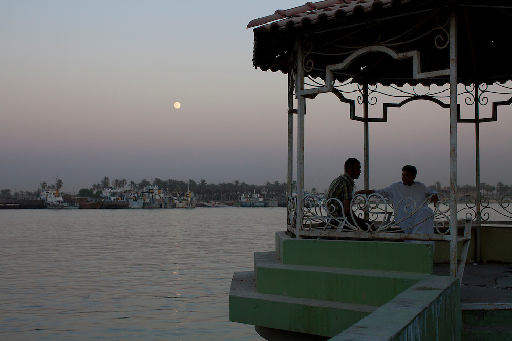 Men watch the moon rise over the Shatt al-Arab on Friday, October 22, 2010 in Basrah, Iraq.