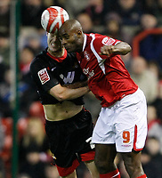 Photo: Steve Bond/Richard Lane Photography. Nottingham Forest v Doncaster Rovers. Coca Cola Championship. 28/11/2009. Dele Adebola (R) gets to the ball at the same moment as Jason Shackell (L)