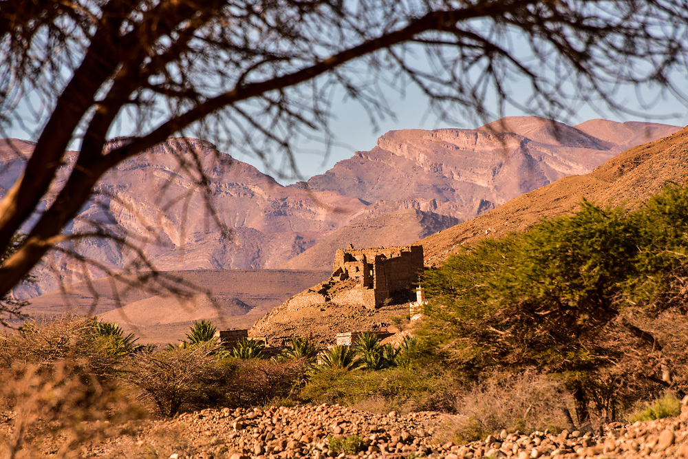 The Atlas Mountains are a mountain range in the Maghreb. It stretches around 2,500 km (1,600 mi) through Algeria, Morocco and Tunisia. The range's highest peak is Jebel Toubkal, with an elevation of 4,167 metres (13,671 ft) in southwestern Morocco. It separates the Mediterranean and Atlantic coastlines from the Sahara Desert. The Atlas mountains are primarily inhabited by Berber populations. The terms for 'mountain' in some Berber languages are adrar and adras, which are believed to be cognates of the toponym Atlas.