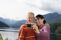 Couple photographing selves mountains in background